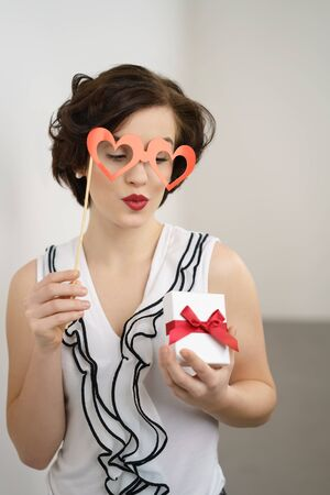 Romantic young woman with a heart shaped glasses party accessory puckering up her lips for a kiss as she looks at a Valentines gift in her hand
