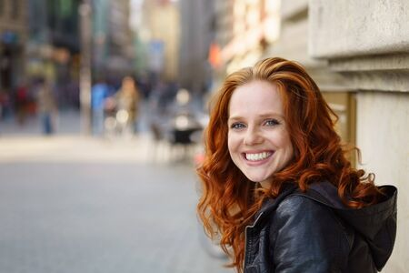 Cute pretty young redhead woman with a cheeky grin standing in an urban street leaning against a wall with copy space