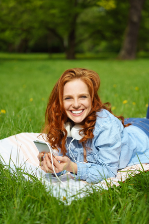 beaming: Pretty young woman relaxing on the grass in a park listening to music on her mobile phone looking at the camera with a beaming friendly smile