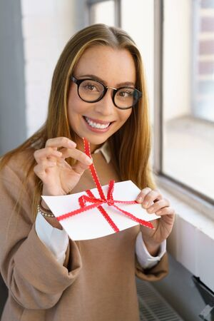 Cute young woman teasing as she opens a gift with a big smile pulling slowly on the red ribbon around the envelope Foto de archivo