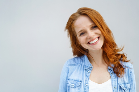 Sincere pretty young redhead woman with a lovely warm friendly smile standing with her head tilted to the side looking at the camera isolated on light grey with copy space Фото со стока