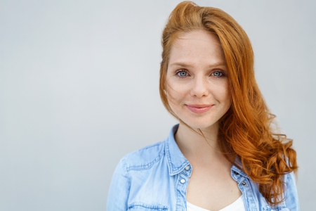 Serene young woman with a quiet relaxed smile and her long red hair over one shoulder in a head and shoulders portrait over light grey with copy space Stock Photo