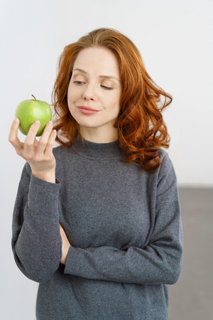 whether: Pensive young woman looking at a fresh green apple she is holding in her hand as she decides whether to eat it or not in a healthy diet concept