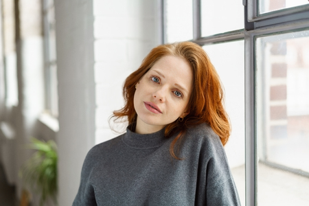 Young pretty redhead woman staring calmly at the camera as she leans against the sill of a large window Stock Photo