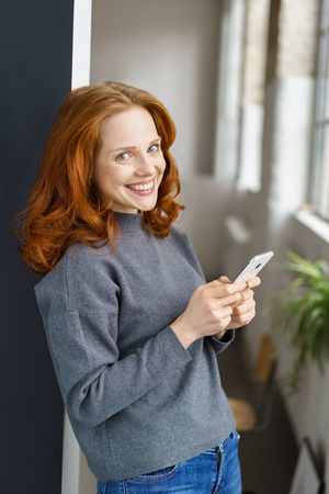 Attractive casual young woman with a big friendly grin standing holding her mobile phone leaning against a door jamb indoors