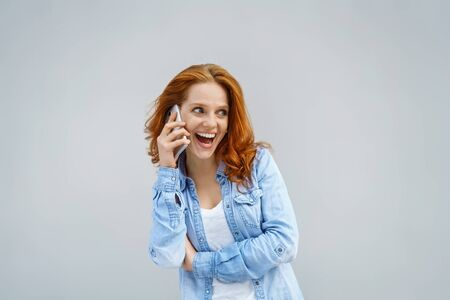 chats: Excited young woman laughing as she chats on a mobile phone looking aside with a wide eyed expression and open smiling mouth