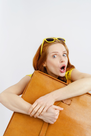 Possessive young woman traveller clutching her brown leather suitcase to her chest while pulling a horrified face with mouth open during a crisis on vacation