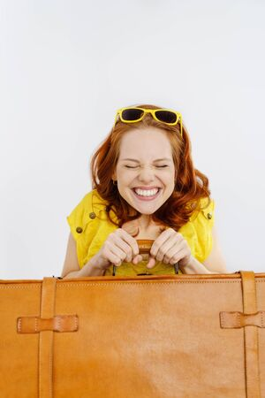 Excited young woman with trendy yellow sunglasses on her summer holidays holding a brown leather suitcase to her chest and screwing up her eyes with a beaming happy grin Stock Photo
