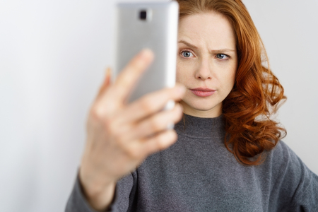 Dubious young woman reading a text message on her mobile phone as she holds it up in her hand with a sceptical expression and raised eyebrow