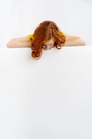 blank space: Redhead woman looking down at a blank sign bending forwards to look at the blank white copy space