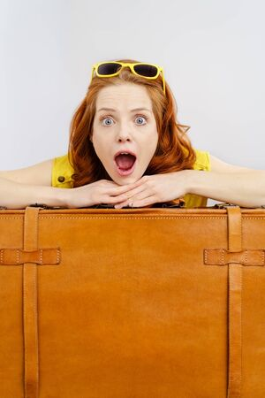 agape: Exuberant excited young woman traveller on summer vacation wearing trendy yellow sunglasses looking at the camera with her mouth agape as she leans on a brown leather suitcase Stock Photo