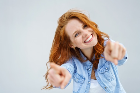 Smiling happy woman pointing at the camera with both hands and her head tilted to the side with a playful expression and focus to her face over grey