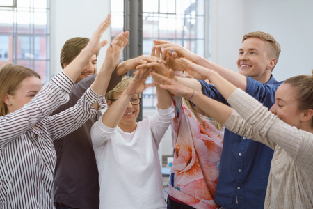 associate: Happy young business team in a motivational meeting raising their hands in unison with beaming smiles in a bright airy office Stock Photo
