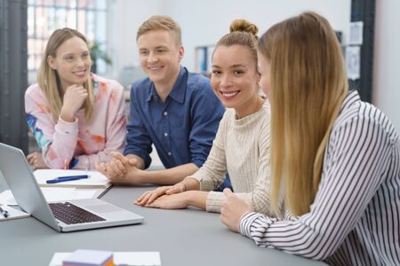 associate: Happy successful female team leader in a meeting with her business colleagues looking at the camera with a beaming smile Stock Photo