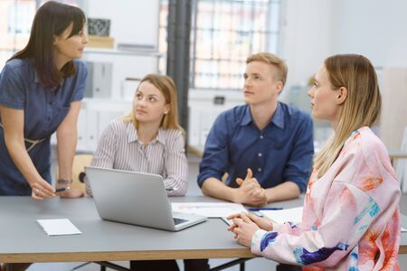 associate: Four colleagues having a serious discussion as they work together as a team in the office listening to one woman as she explains something Stock Photo