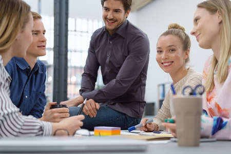 Happy successful group of young people having an informal business meeting grouped around a table with one young man sitting on the top and focus to a smiling woman