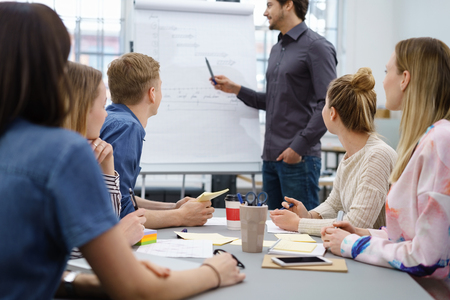 Businessman giving a presentation to colleagues pointing to a flip chart as they sit around a table watching him with focus to the audience Stock Photo