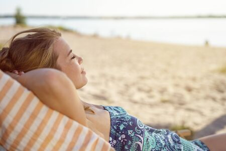 Young woman dozing in a deckchair on the beach