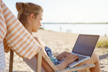 Young woman typing on a laptop on a beach Standard-Bild - 81036852