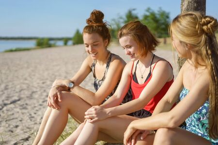 Three attractive young ladies relaxing at a beach Stock Photo