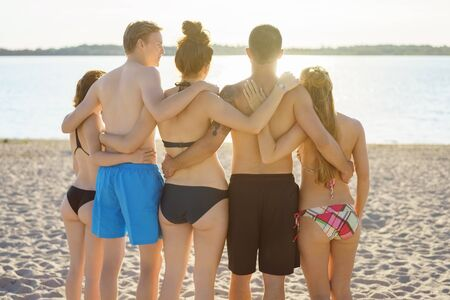 Rear view of a group of people on a beach photo