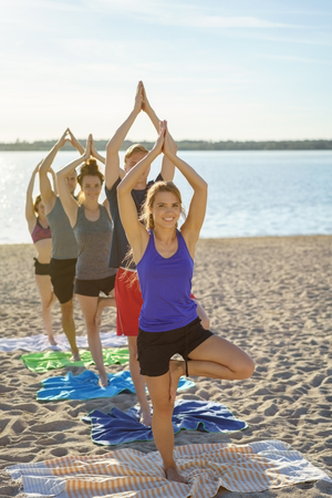 Healthy young people practicing yoga on a beach photo