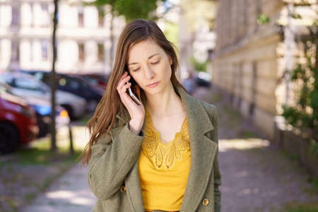 Sad depressed young woman listening to a call on her mobile phone with a serious downcast expression as she walks trough town Stock Photo
