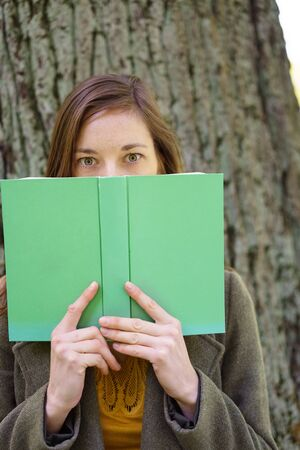 Young woman hiding behind a large green hardcover book with jst her eyes staring at the camera over the top outdoors in the garden Reklamní fotografie