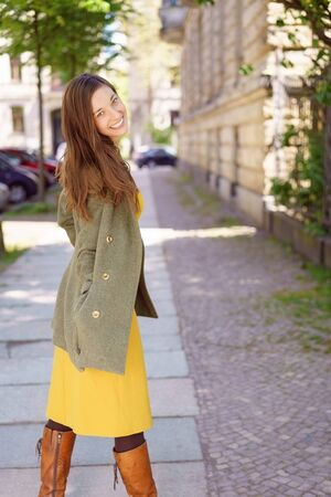 beaming: Stylish sexy young woman on an urban sidewalk turning to grin provocatively at the camera with a beaming smile