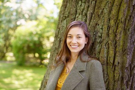 Friendly young woman with a warm smile standing leaning against a tree trunk in a green park in spring Stock Photo