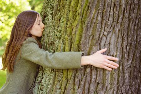 Giovane donna che abbraccia e bacia il tronco d'albero, concetto ambientale