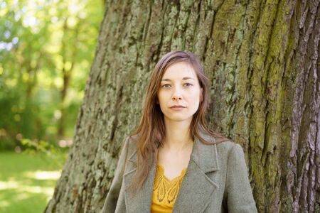 Head and shoulder portrait of young woman by tree in green countryside