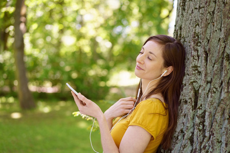 net: Young woman enjoying a quiet moment alone in a leafy green park listening to music on her mobile phone as she leans against a tree with her eyes closed