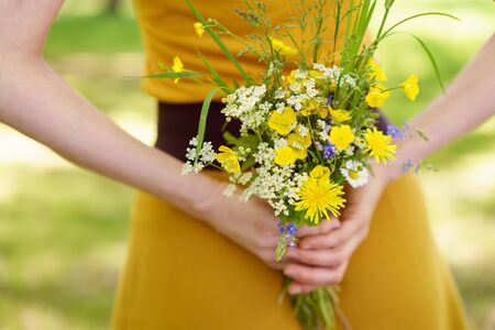 Woman hiding a posy of fresh yellow and white spring flowers behind her back as she stands outdoors in the garden in a close up cropped view of her hands