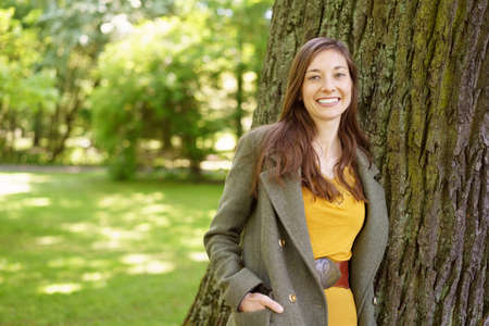 Stylish friendly young woman walking in a park passing the trunk of a tree with her hands in her pockets smiling at the camera