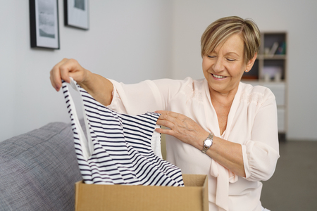 Portrait of cheerful senior woman taking out clothes from cardboard box