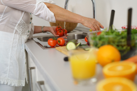 Woman washing tomatoes in kitchen sink before putting them into vegetable salad Zdjęcie Seryjne