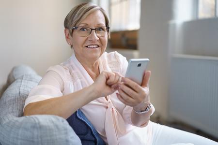ソファに腰掛けながらスマート フォンを使用して陽気な年配の女性の肖像画