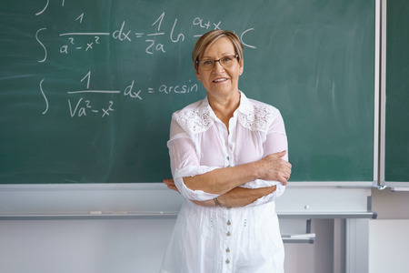 Portrait of female senior teacher standing against blackboard with mathematical formulas in classroom Stockfoto
