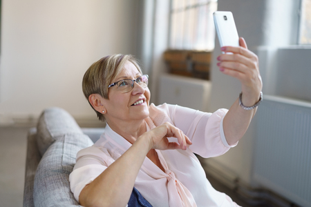Portrait of smiling senior woman taking selfie with smartphone