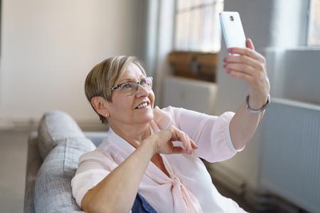 Retrato, de, sorrindo, mulher sênior, levando, selfie, com, smartphone Foto de archivo - 83561450