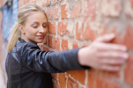 Serene young woman taking a relaxing moment to herself standing facing a brick wall with outstretched arm and her eyes closed
