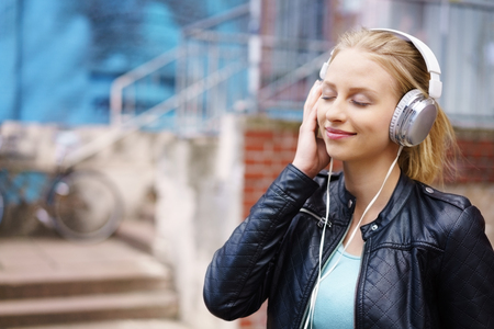 Fashionable young woman wearing black leather jacket while listening to music through headphones outdoors on the street