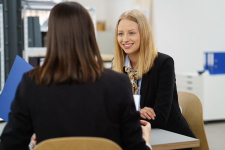 Two female colleagues in a business meeting sitting together at a table in the office in an over the shoulder view of a smiling young woman photo
