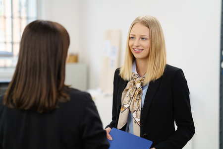 Hopeful young woman in a job interview listening to the female interviewer with a thoughtful smile as she holds her CV photo