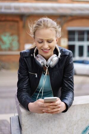 Young woman standing leaning on an exterior wall in town browsing on her mobile phone selecting music to listen to with a smile Stock Photo