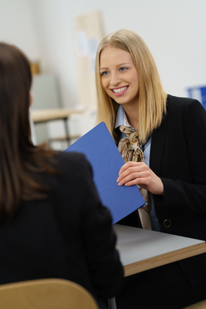 Young job applicant handing over her CV with a wide friendly smile to the interviewer in an over the shoulder view photo