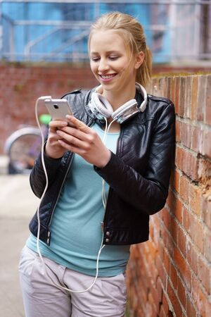 Trendy young woman listening to music on her mobile phone standing leaning against on exterior brick wall with a smile