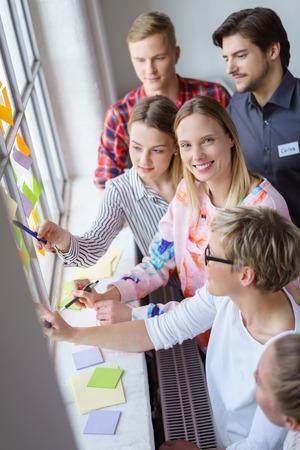 Un equipo de colegas de trabajo felices compartiendo ideas y el asalto al cerebro con notas adhesivas durante una reunión en una oficina con mucha luz.