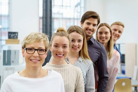 A happy, smiling office work team in an ascending order style portrait in a bright office setting.